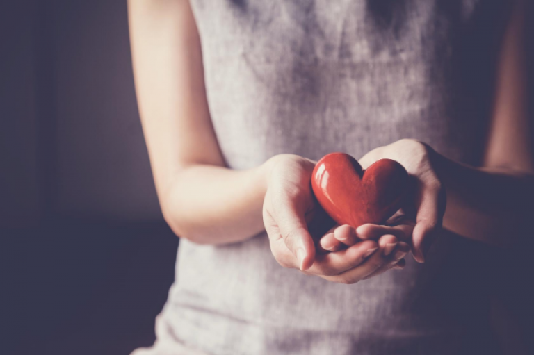 woman holding ceramic red heart in hands