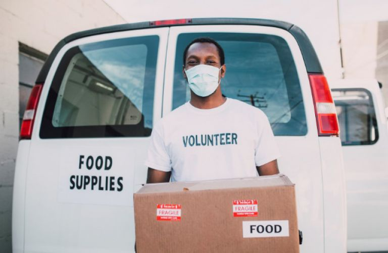 Volunteer wearing a mask carrying food to give out to those in need